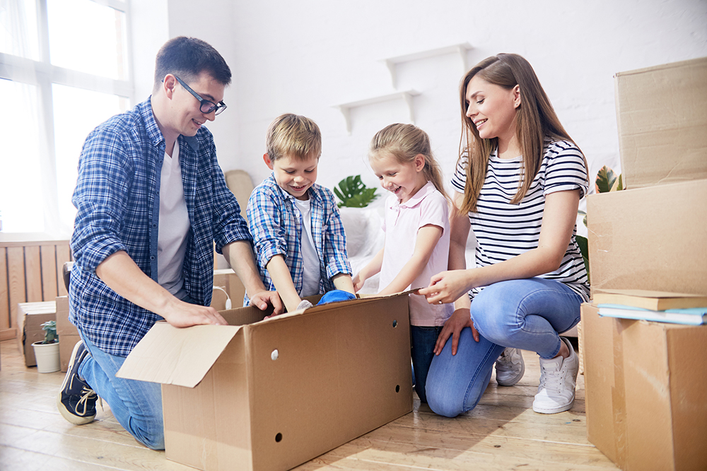 Cheerful young family gathered together at spacious living room of new apartment and enthusiastically unpacking moving boxes with their stuff