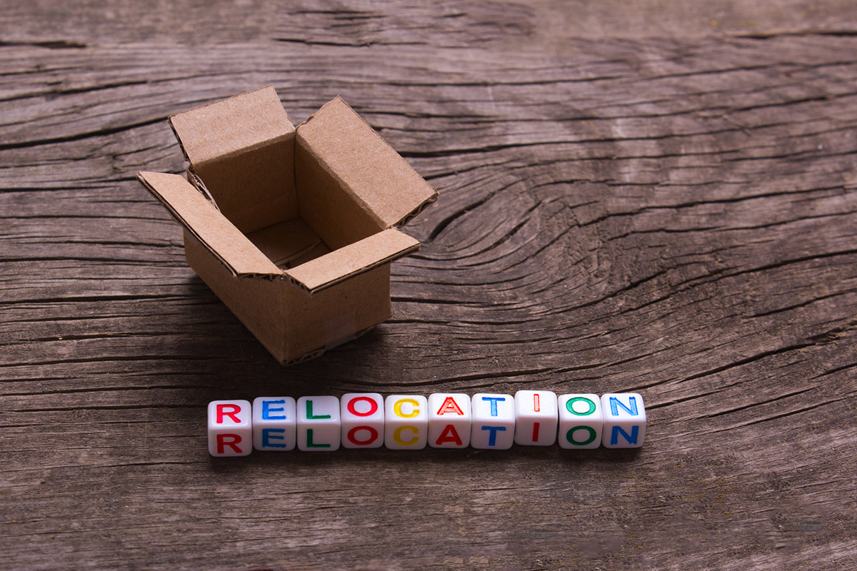 Moving to another office or house. Word relocation on an old wooden background